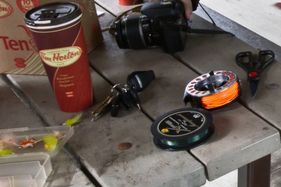 A picture of a fly wheel, fly line, and Tim Horton's coffee